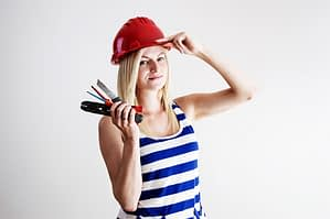 Beautiful woman wearing red hard hat holding a pair of pliers and a cutter