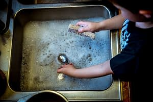 A kid washing the dishes