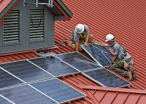 people installing solar panel on roof